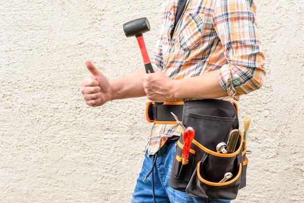 Рабочий держит резиновый молоток.