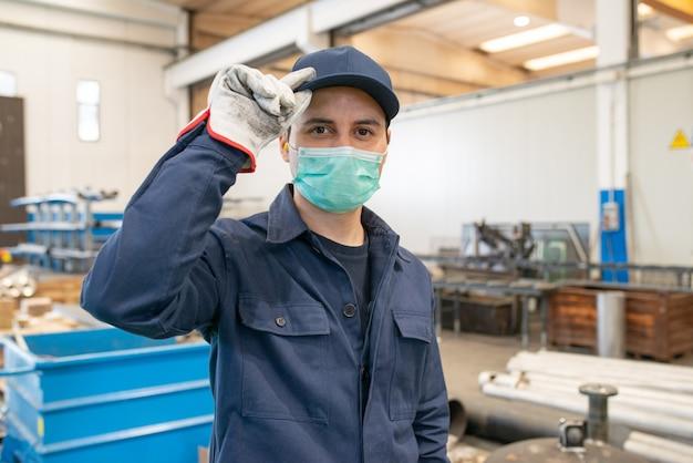 Рабочий на фабрике в маске и держит защитную шляпу