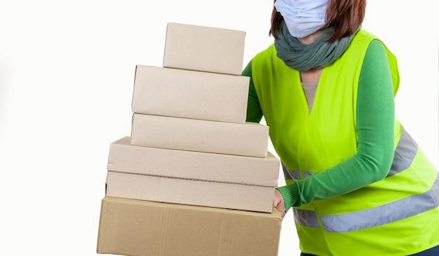 たくさんの紙箱を持っている緑のベストの労働者、配達の概念。