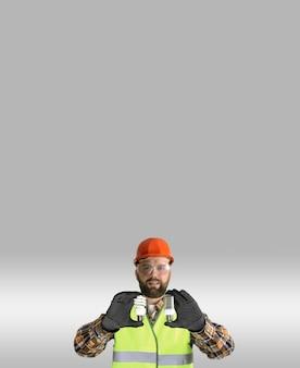 Рабочий в шлеме и защитной одежде с лампочкой в руках на сером фоне