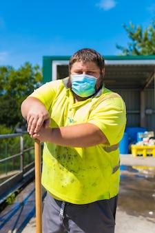 Работник фабрики по переработке отходов или чистой точки и мусора в маске и с защитными приспособлениями. портрет рабочего с метлой