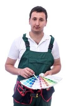 白で隔離色見本を保持しているつなぎ服の労働者