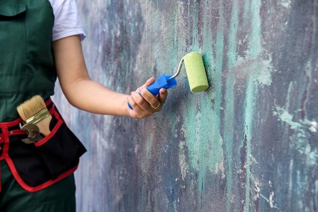 緑色のローラーでカバーオール塗装壁の労働者をクローズアップ