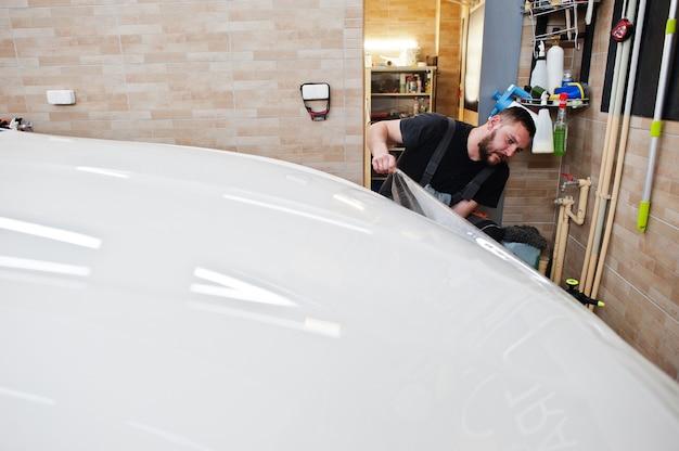 디테일링 차고의 작업자는 흰색 고급차에 폴리우레탄 자갈 방지 필름 커버를 넣었습니다.