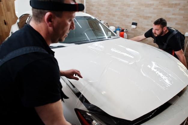 ガレージのディテールを担当する作業員が、ポリウレタン製の砂利防止フィルムカバーを白い高級車に取り付けました。