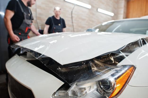 Рабочий при отделке гаража кладет полиуретановую антигравийную пленку в белый люксовый автомобиль.