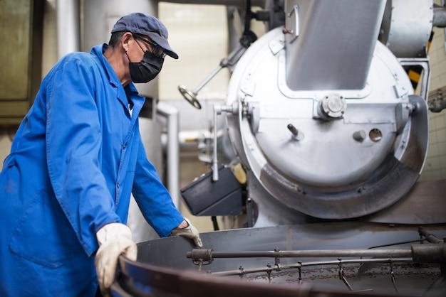 コーヒーの焙煎プロセスを制御するフェイスマスクの労働者。焙煎装置に取り組んでいるコーヒー焙煎業者。マスクと制服を着た男機械器具での作業
