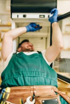 手袋と制服を着た労働者が自宅で冷蔵庫を修理します。