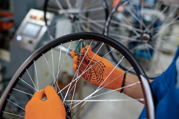 작업자가 장갑을 끼고 공장에 새 자전거 스포크를 설치합니다. 작업장에서 자전거 바퀴 조립, 사이클 부품 설치, 현대 기술