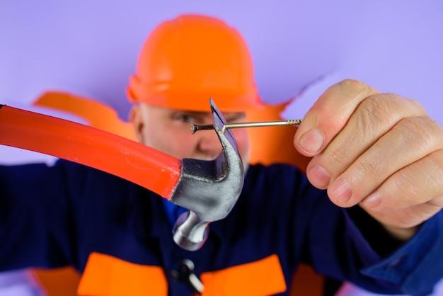 ハンマーと釘を持ったヘルメット労働者の労働者修理工ハンマーと釘ビルダーの広告