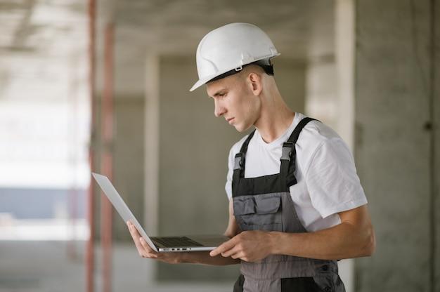 노트북에서 일하는 하드 모자에있는 노동자