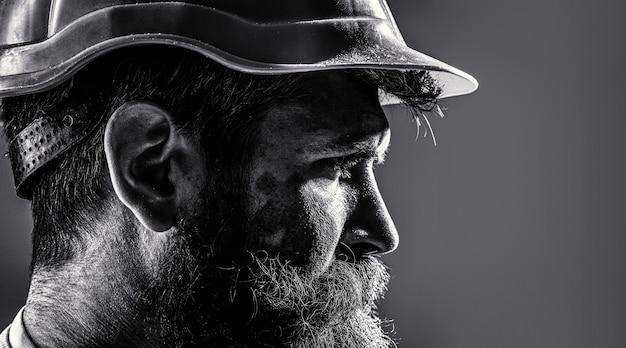 Рабочий в каске. портрет механика. бородатый мужчина в костюме со строительным шлемом. портрет красивого инженера. строитель в каске, прораб или ремонтник в каске. черное и белое.