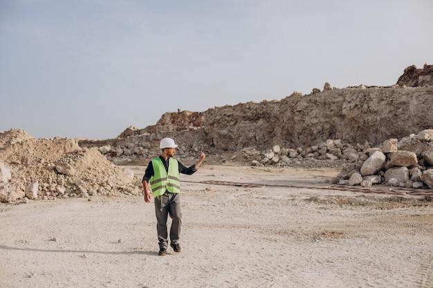 모래 채석장에 서 있는 안전모 작업자