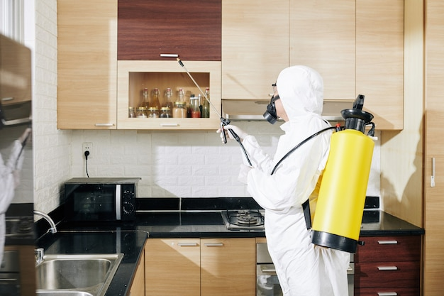Работник в костюме hazmat, наносящий спрей на поверхности