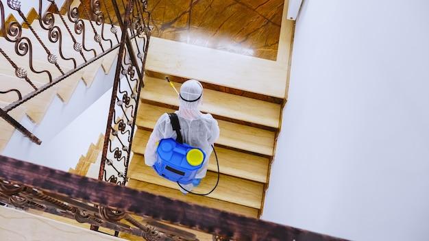 Рабочий в костюме hazmat распространяет дезинфицирующее средство на офисном здании против распространения коронавируса.