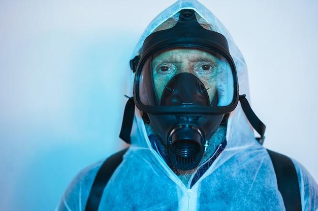 都市の建物内で消毒を行いながら顔の防毒マスク保護を身に着けている防護服の労働者 Premium写真
