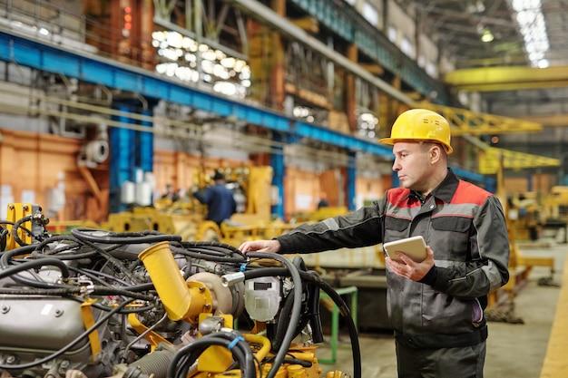 태블릿 pc를 사용하여 헬멧을 쓰고 공장에서 기계 장비를 검사하는 작업자