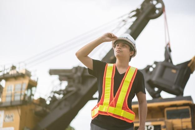 Рабочий на добыче лигнита или угля с грузовиком, перевозящим уголь.