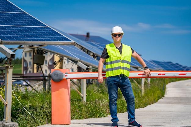 Работник фермы базы новой энергии. техник на фоне панелей солнечных батарей.
