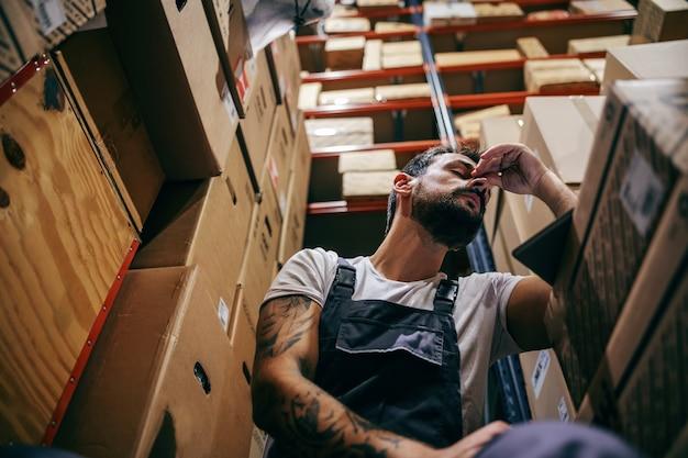 Рабочий в спецодежде, тяжелый день на работе. хранение импортных и экспортных фирменных интерьеров.