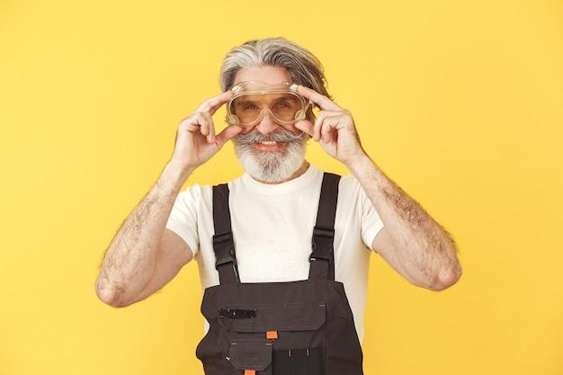 작업 바지에있는 노동자. 도구를 가진 남자. 노란색 안경에 수석입니다.