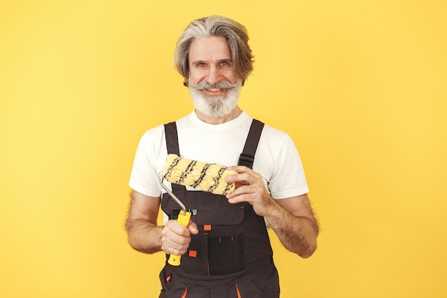 Рабочий в спецодежде. человек с инструментами. старший с малярным валиком.