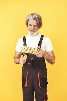 작업 바지에있는 노동자. 도구를 가진 남자. 페인트 롤러와 수석.