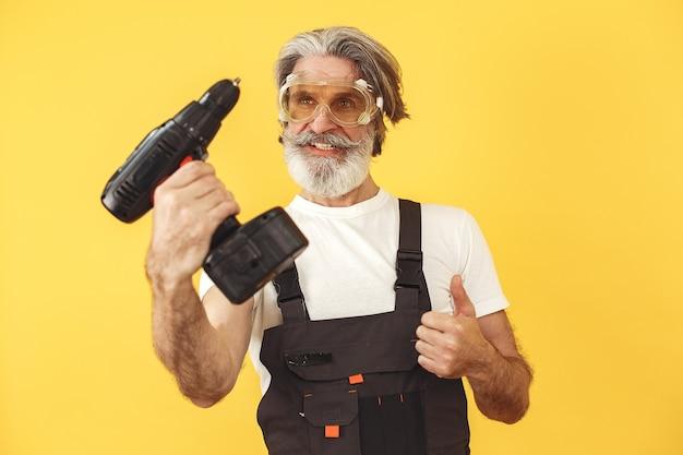 작업 바지에있는 노동자. 도구를 가진 남자. 드라이버와 함께 수석입니다.