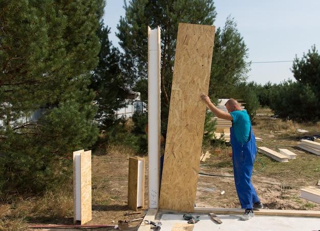 새 집의 건축 현장에 단열된 나무 벽 패널을 세우고 서 있는 작업복을 입은 작업자