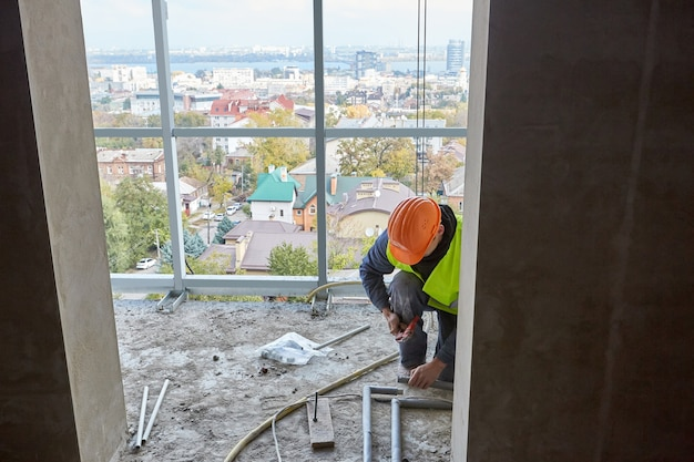 建設中の建物のフラットに最新のツールを使用してプラスチックパイプを設置する保護服と安全ヘルメットの労働者