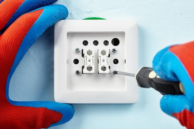 보호 장갑을 입은 작업자가 새로운 유럽 표준 푸시 버튼에서 나사를 비틀고 있습니다.