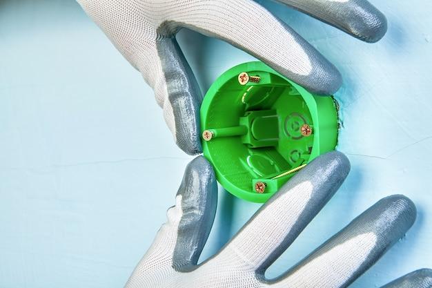 벽 조명에 대 한 둥근 콘센트 상자를 장착하는 보호 장갑에 노동자.