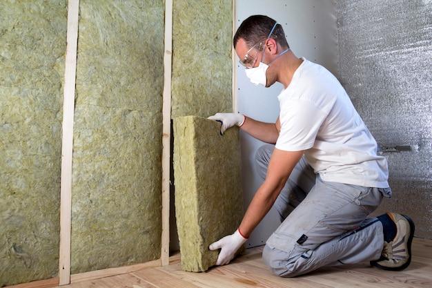 Работник в защитных очках и респираторе изолирует минеральную вату в деревянном каркасе для будущих стен дома от холодного барьера. комфортный теплый дом, экономика, строительство и ремонт концепция