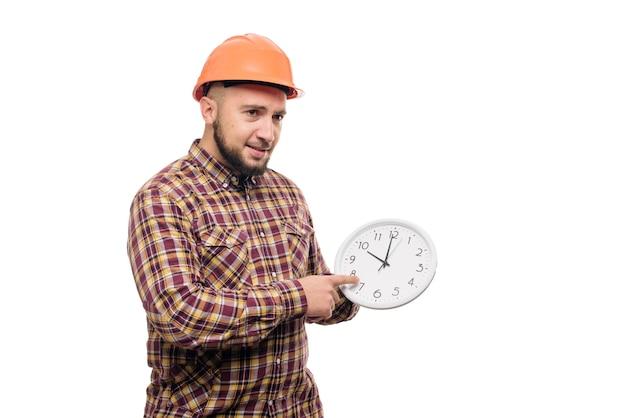 白の目覚まし時計を保持している保護ヘルメットの労働者。働く時間。建物の建設時間