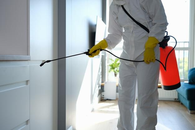 Рабочий в защитной спецодежде и перчатках, дезинфицирующих квартиру