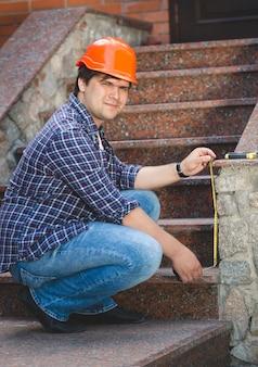 古い石の階段を修理する赤いヘルメットの労働者