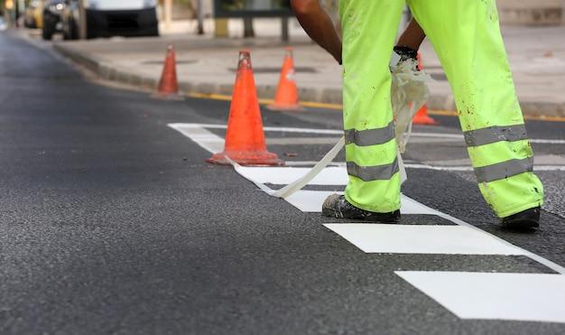 반사 바지를 입은 작업자가 도로 공사에서 열가소성 마킹 테이프를 제거하여 교통선을 페인트합니다