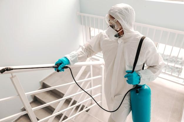 Работник в стерильной форме, в перчатках и маске стерилизует перила в школе.