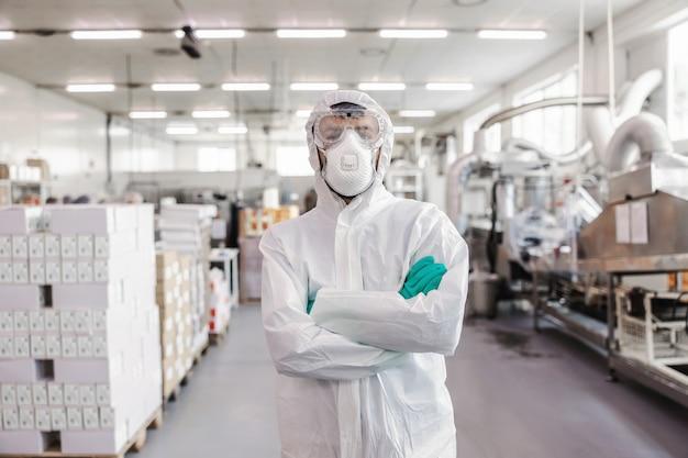 Рабочий в стерильной форме с резиновыми перчатками держит распылитель с дезинфицирующим средством и распыляет по складу. концепция вспышки короны.