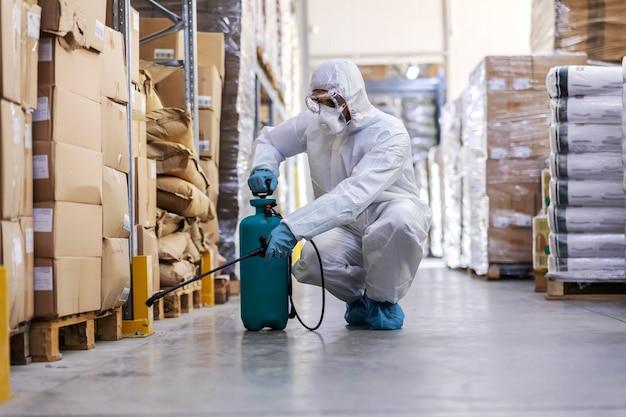 消毒剤付きの噴霧器を保持し、倉庫の周りに噴霧するゴム手袋を着用した無菌の制服を着た労働者。コロナ発生の概念。