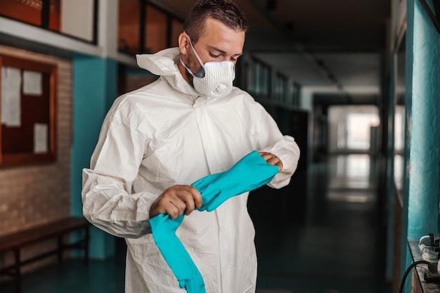 Рабочий в стерильной белой форме снимает резиновые перчатки, стоя в коридоре школы после дезинфекции.