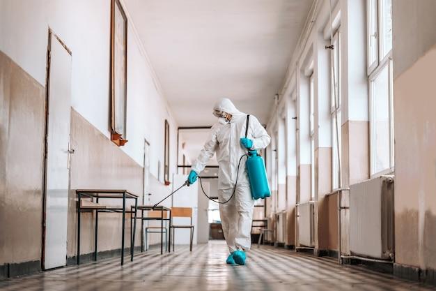 Рабочий в стерильной белой форме, в маске и очках держит распылитель с дезинфицирующим средством и опрыскивает коридор в школе. предотвращение распространения вируса короны.