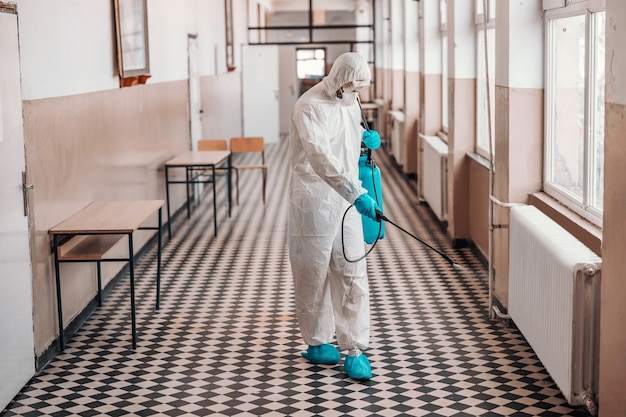 Работник в стерильной белой униформе, в маске и очках держит распылитель с дезинфицирующим средством и опрыскивает коридор в школе