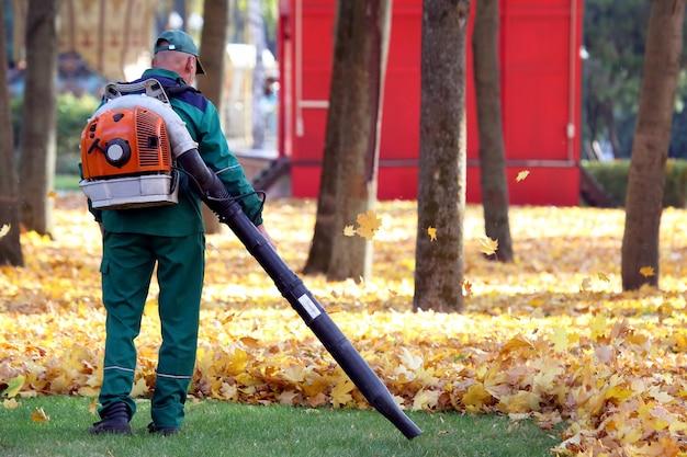 Рабочий в парке очищает траву от опавших листьев с помощью ветряной турбины