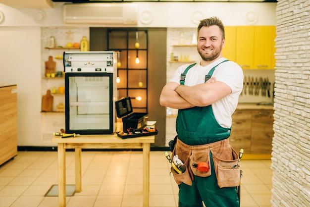 Рабочий в униформе против холодильника на столе