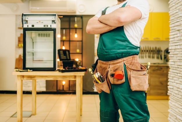 自宅のテーブルの上の冷蔵庫に対して制服を着た労働者。冷蔵庫の修理、専門サービス