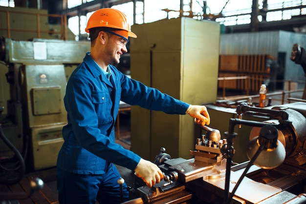 Рабочий в форме и каске работает на токарном станке, фабрике. промышленное производство, слесарное дело, производство силовых машин.