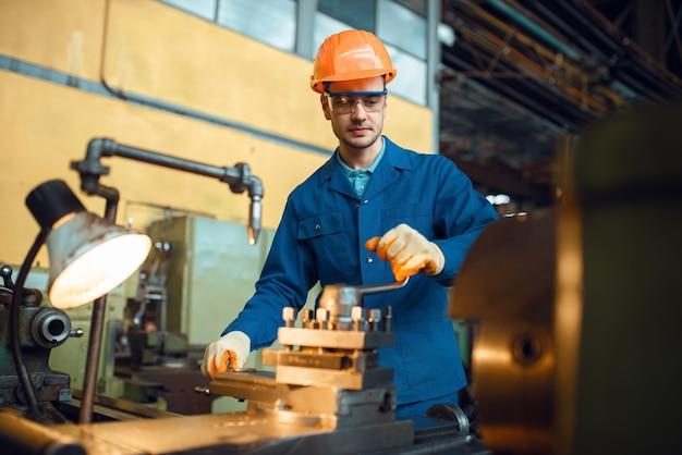 Рабочий в форме и шлеме работает на токарном станке, завод