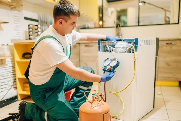 제복을 입은 작업자가 집에서 냉장고 압축기를 채 웁니다. 냉장고 직업 수리, 전문 서비스