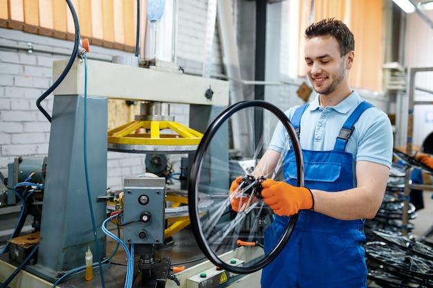 제복을 입은 작업자는 공장에서 공작 기계 근처 자전거 바퀴를 보유하고 있습니다. 작업장에서 자전거 림 및 스포크 조립, 사이클 부품 설치, 현대 기술